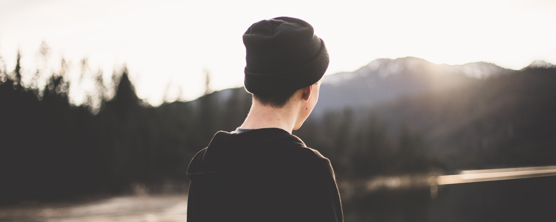 A boy with a black beanie watching a river landscape. The sun shines on his face from behind the mountains in the background.