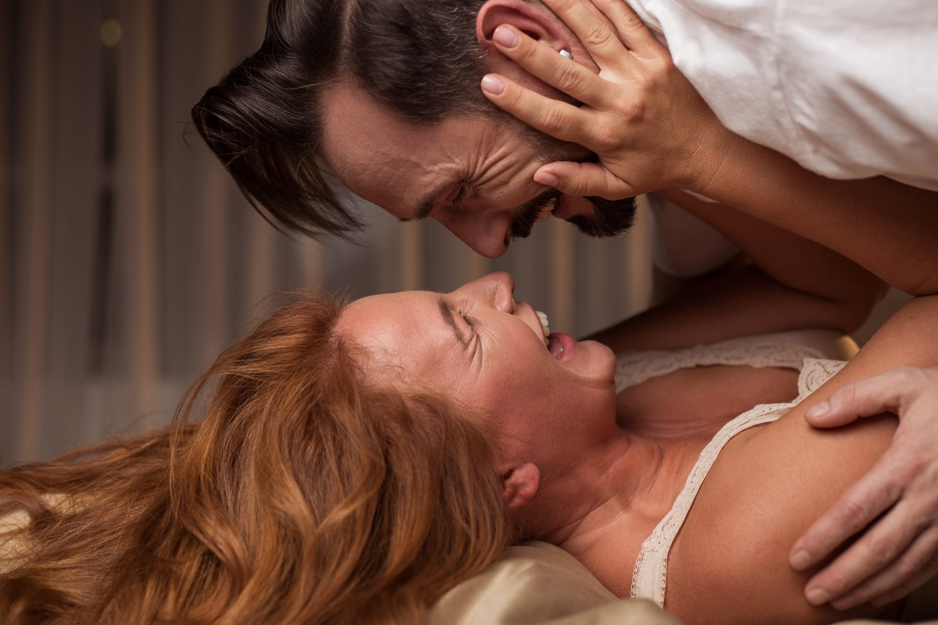 A middle-aged couple holding each other and laughing while lying in bed.