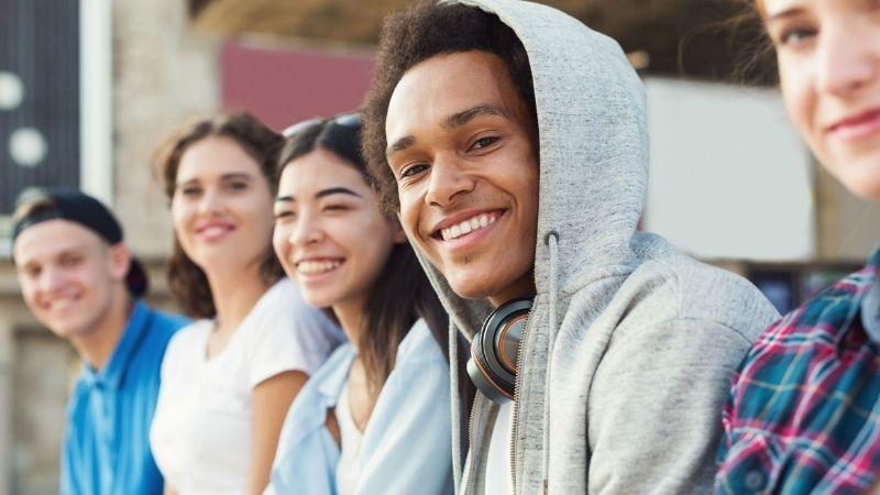 Viisi nuorta istuu ulkona tiiliseinän edessä rivissä ja hymyilevät kameraan.