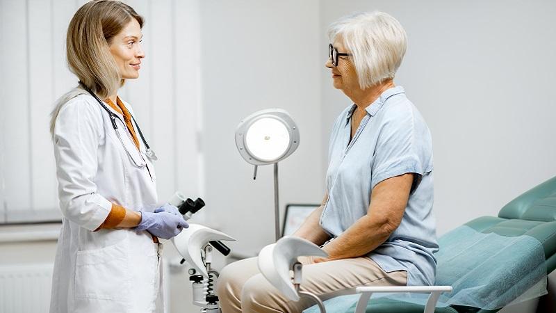 nainen istuu gynekologin pedillä ja katsoo lääkäriä