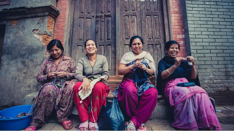 neljä naista istuu rappusilla ja kutoo
