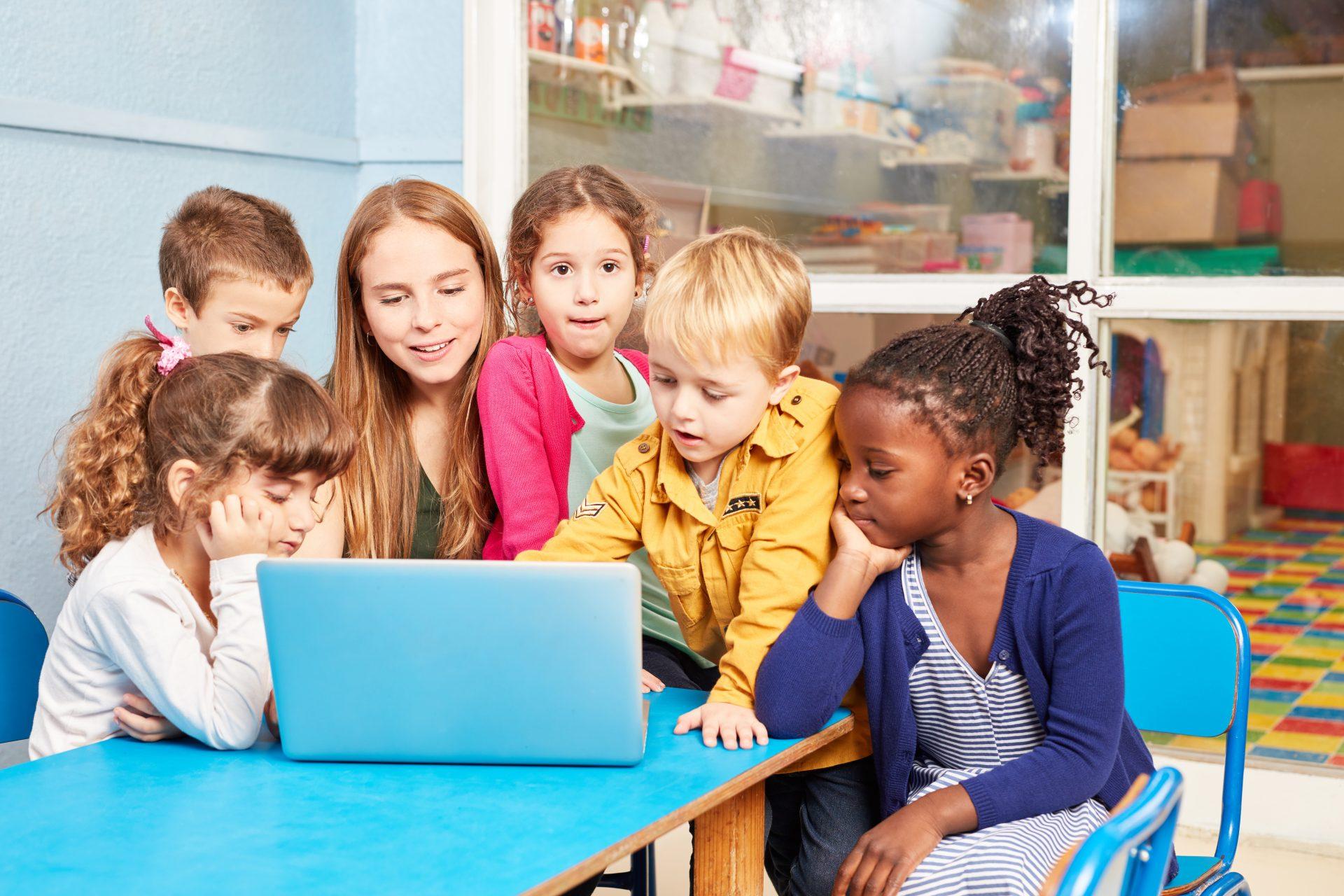 Lapset katsovat jotain yhdessä tietokoneelta.