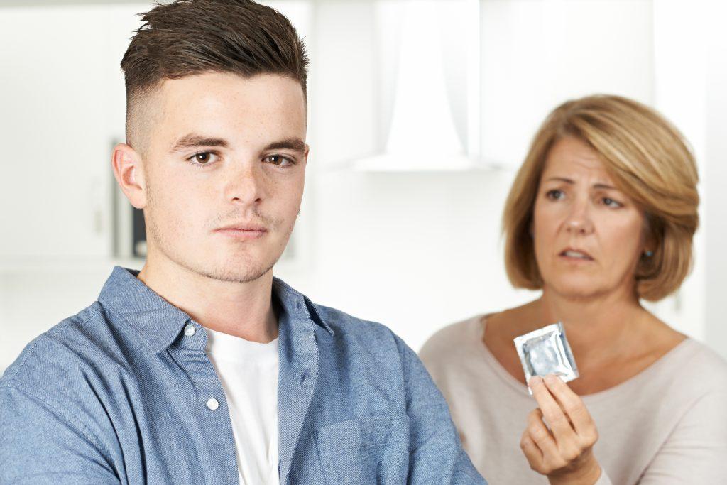 Poika katsoo kameraan, vanhempi  nainen pitää kondomia huolestuneen näköisenä.