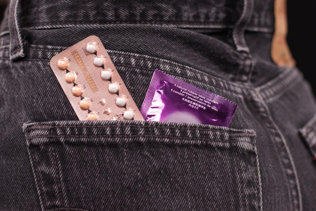 farkkuhousun tasku, jossa on e-pillerit ja kondomi