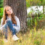 Nuori tyttö istuu mietteissään maassa ja nojaa puhun.
