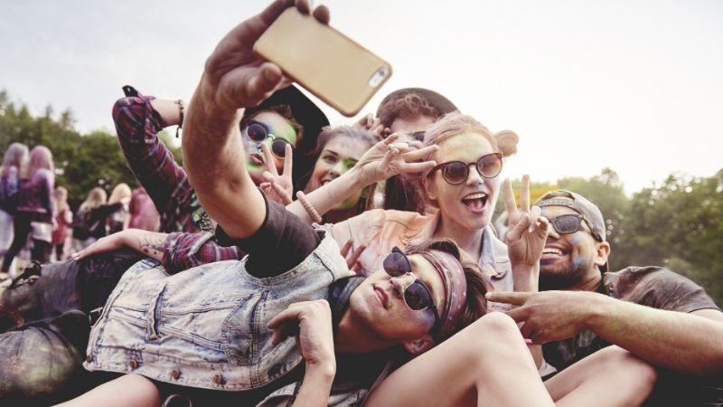 Iso joukkoa nuoria makaa ulkona maassa, auronkolasit päässä ja ottavat selfietä.