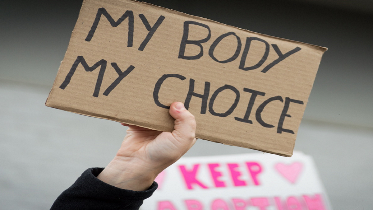 hand holding sign: body my choice