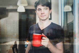 Nuori mies kahvikuppi kädessä.