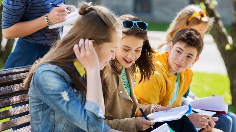 Yläkoululaiset istuvat ulkona penkillä ja juttelevat koulukirjat käsissä.