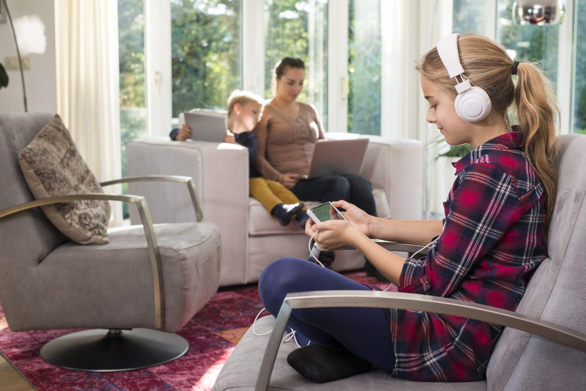 Äiti ja kaksi lasta olohuoneessa tietokoneilla ja puhelimilla.