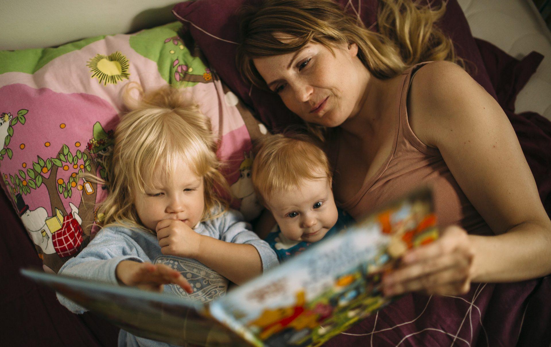 Mamma läser till sina barnen.