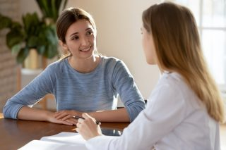 kaksi nuorta naista keskustelee pöydän ääressä, katsovat toisiaan. Toinen on kääntänyt katseensa poispäin kämerasta, toisen kasvot näkyvät kokonaan.