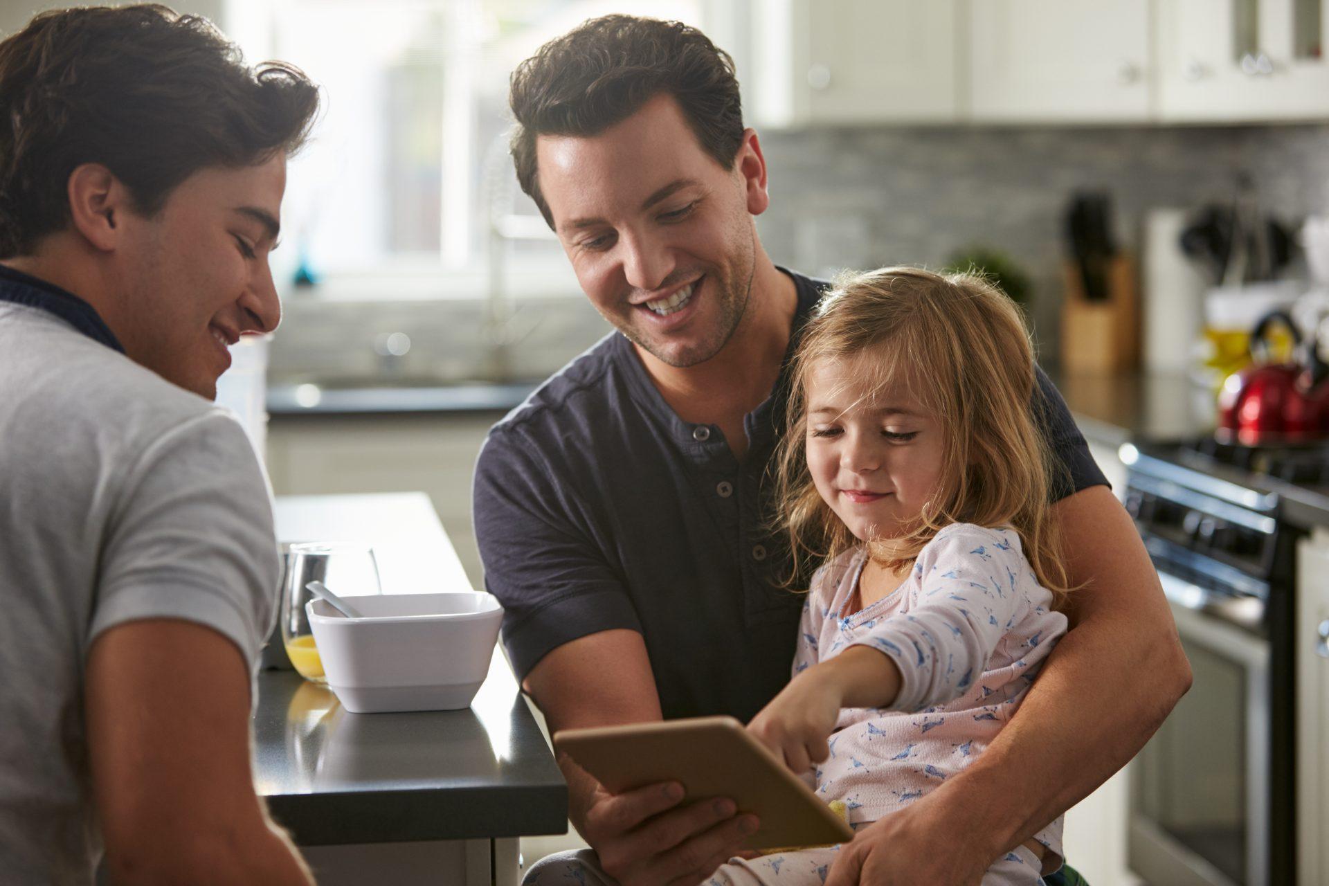 Kaksi isää ja lapsi juttelevat keittiössä.
