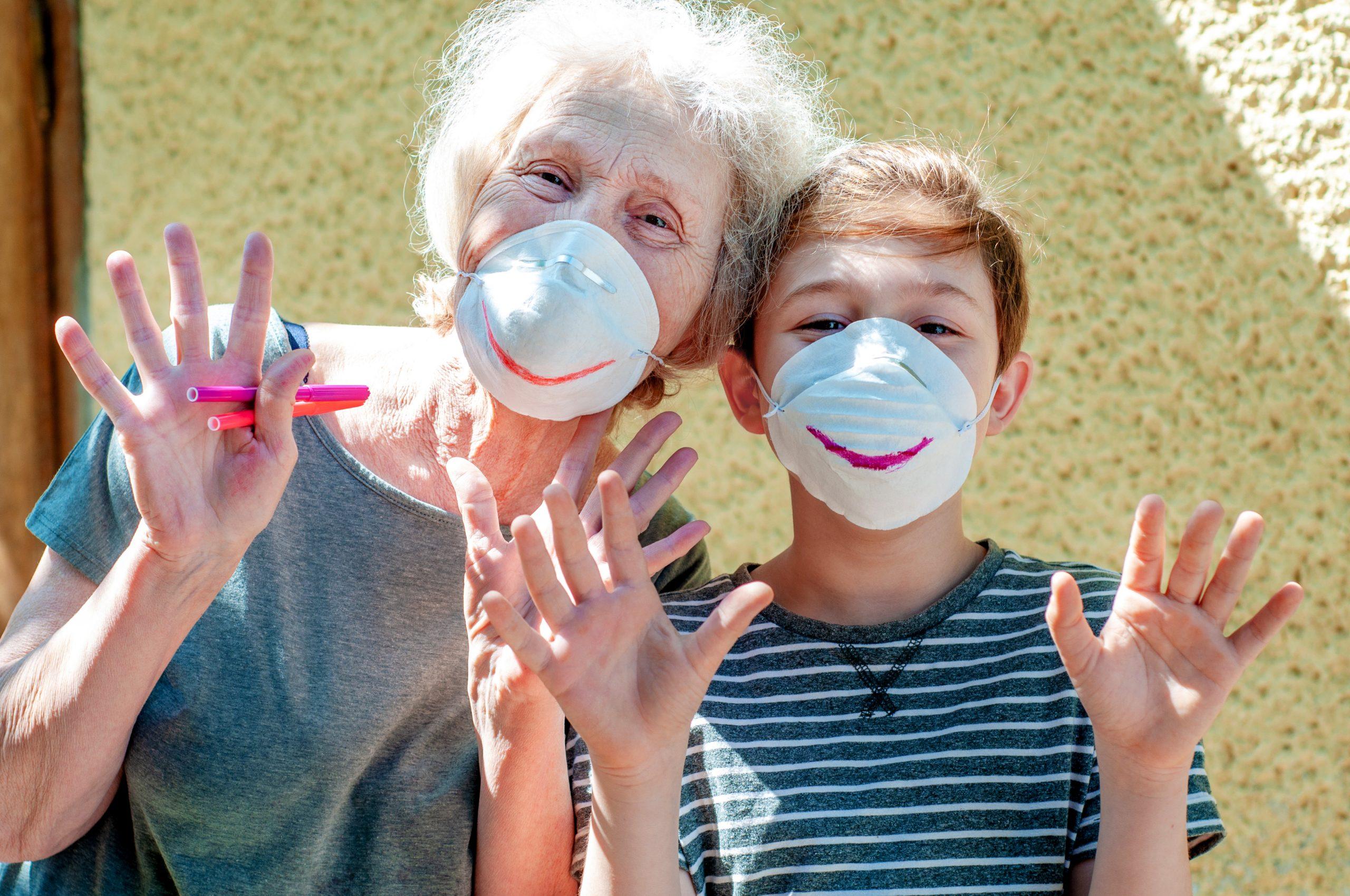 Isoäiti ja poika katsovat kameraan. Heillä on kasvomaskit, joihin ovat piirtäneet hymyilevät suut.