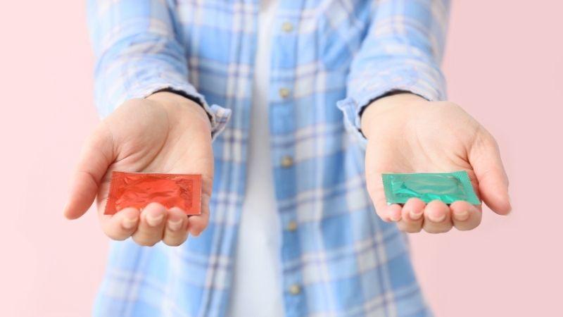 Kuvassa näkyy henkilön kehon yläosa ja kädet ojennettuna vaaleanpunaisen seinän edessä. Molemmissa käsissä on kondomi.