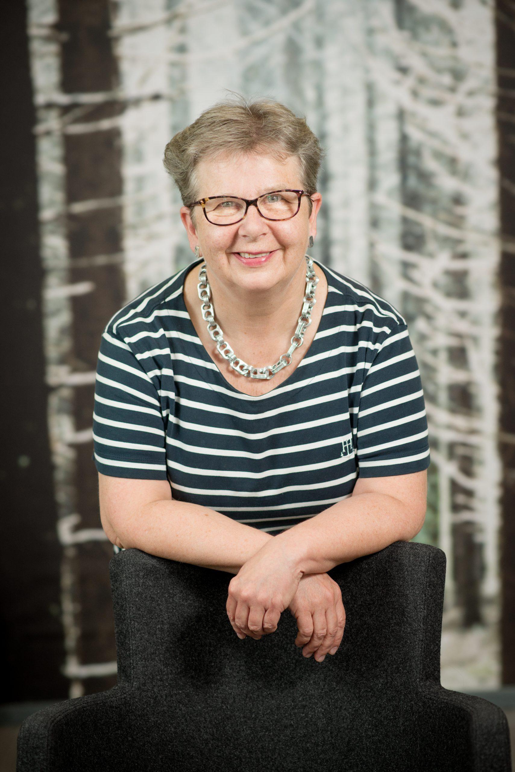Susse Inglman-Fribergin ylävartalon kokoinen kuva, jossa nojaa tuoliin. Raidallinen paita ja hopeanvärinen koru kaulassa.