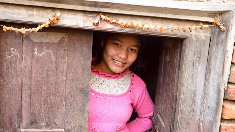girl smiles in a doorstep