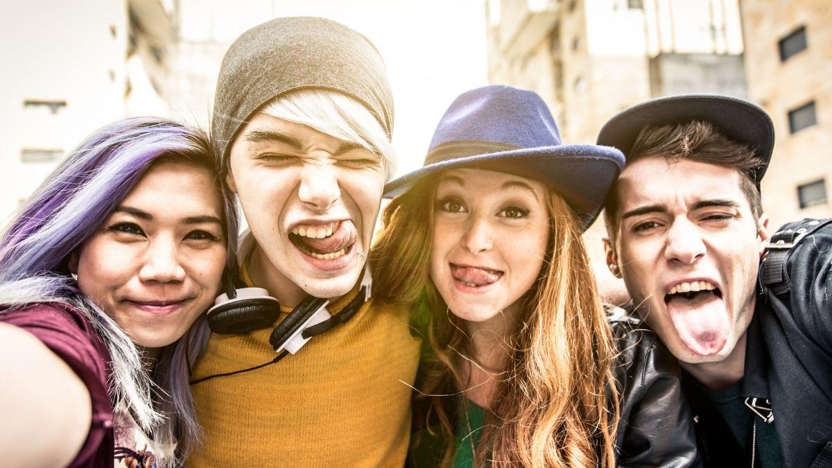 Neljä nuorta illistää kuvassa iloisesti.