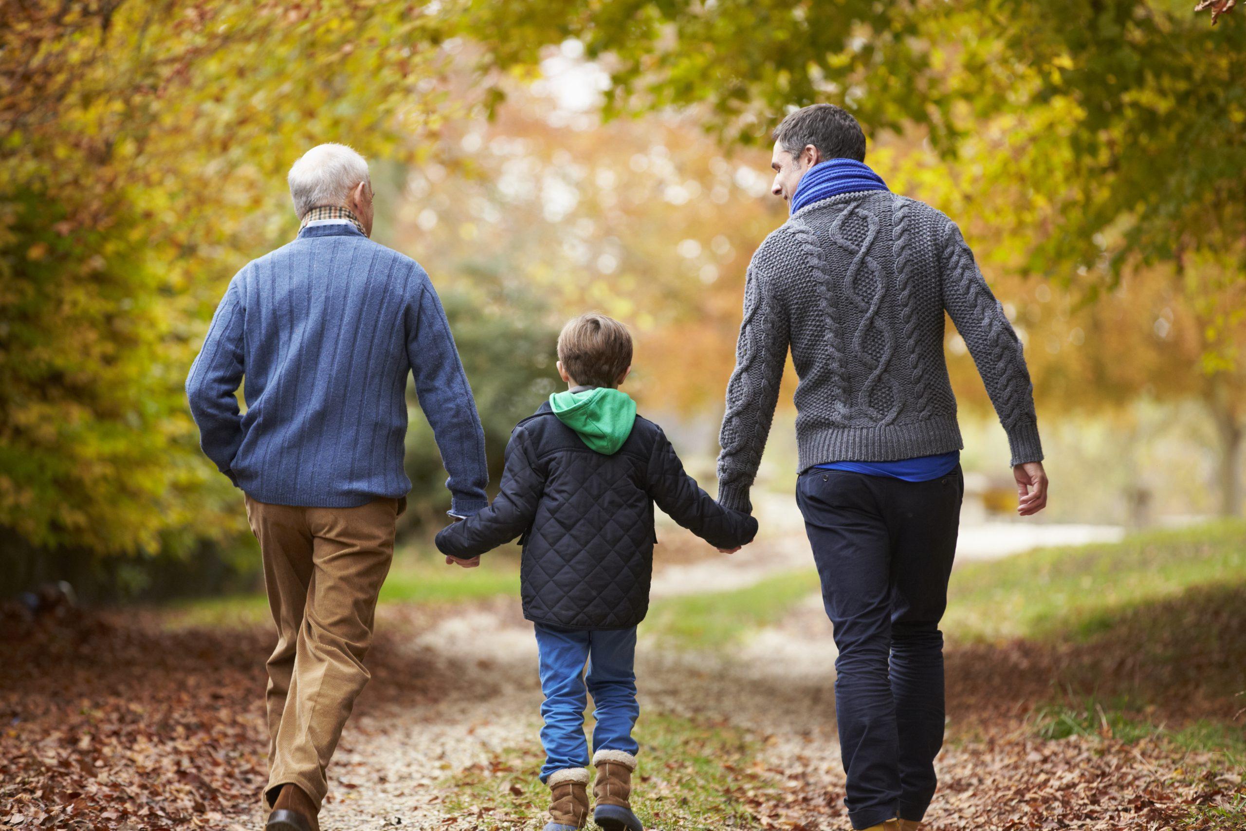 Isoisä, isä ja poika kävelevät syksyisessä metsässä poispäin kamerasta.