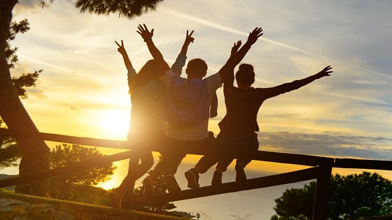nuoret kädet ylhäällä oksalla aurongonlaskuun päin
