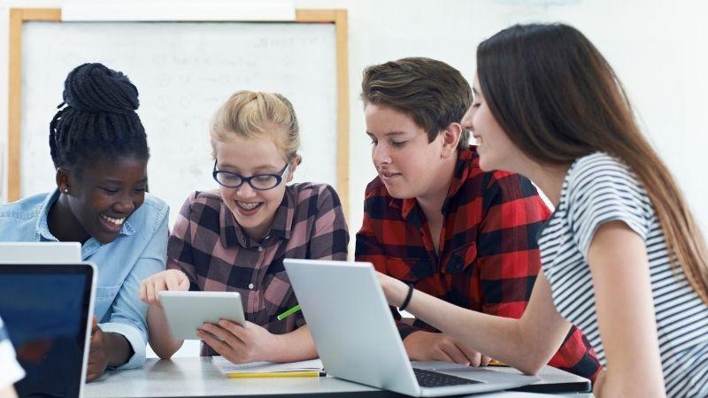 Hymyileviä nuoria oppitunnilla koulussa. Istuvat pöydän ääressä läppärit pöydällä ja katsovat yhdessä yhden nuoren näyttämään vihkoa.