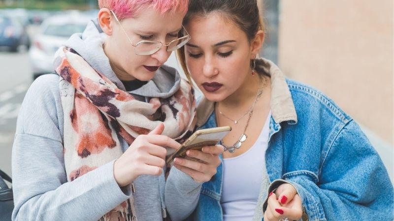 Kaksi meikattua nuorta katsoo toisen nuoren puhelimen näyttöä kadulla.