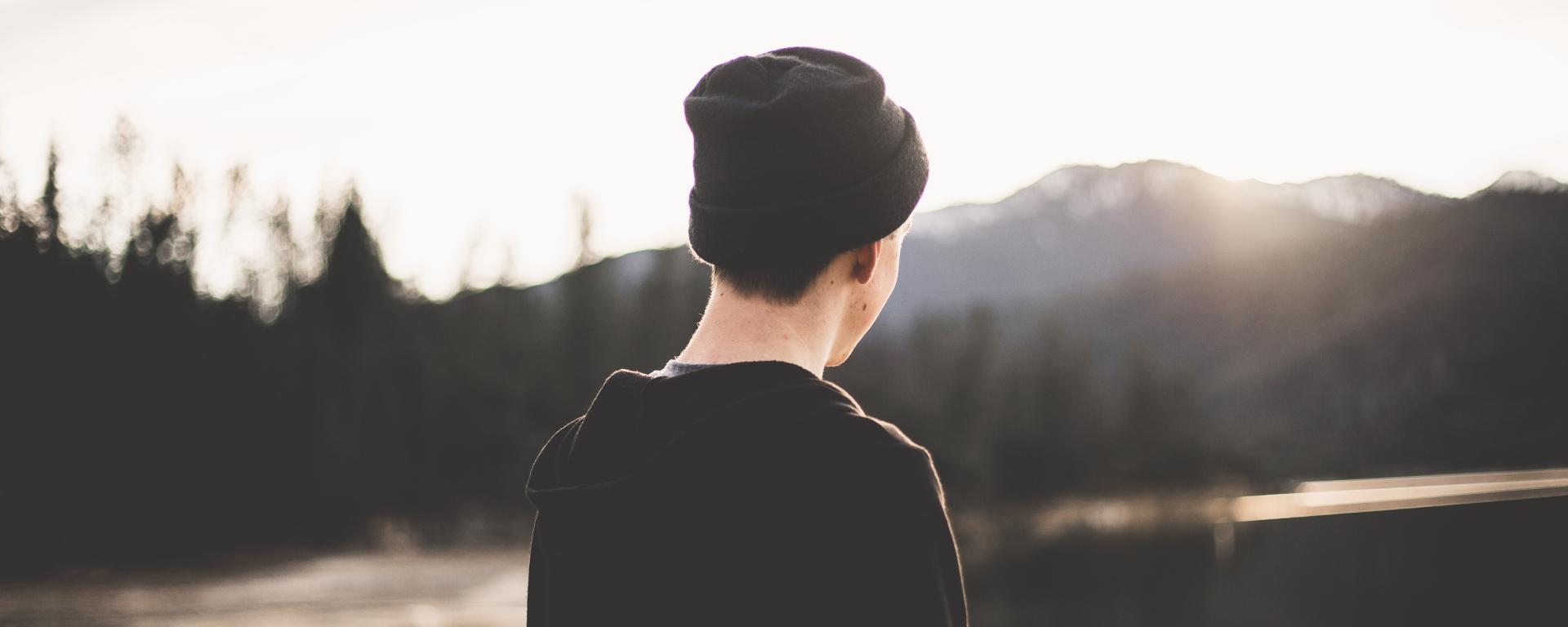 Poika seisoo selin musta pipo päässään katsellen maisemaa, jossa joki ja vuori. Aurinko paistaa hänen kasvoihin vuorten takaa.