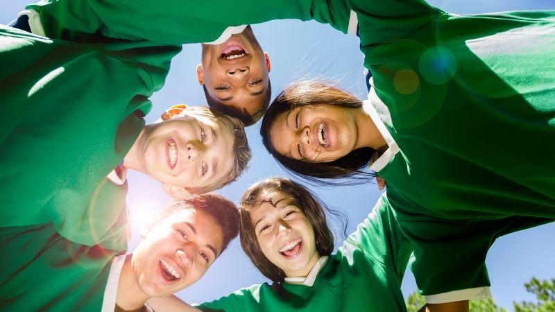 Urheiluseuran nuoret seisovat ringissä alaspäin kameraan katsoen ja huutaen iloisesti. Sininen taivas taustalla.