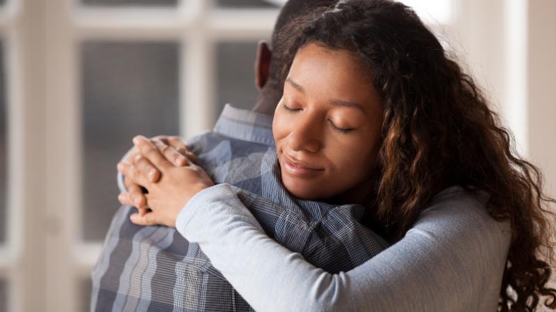 Mies ja nainen halaavat. Kuvassa näkyy naisen onnelliset kasvot, silmät kiinni. Miehestä näkyy sellkää ja takaraivoa. Molemmat näyttävät afrikkalaistaustaisilta.