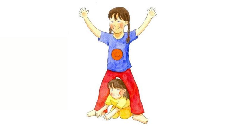 Pieni lapsi ryömii isomman lapsen haarojen välistä. Molemmat lapset ovat iloisia.