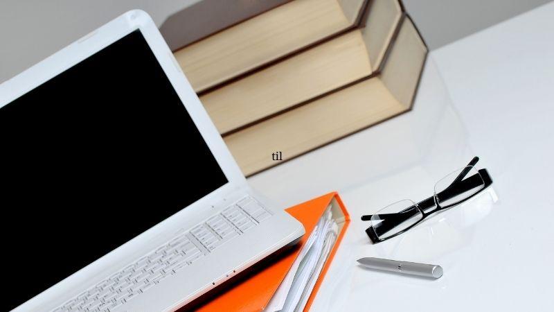 Pöydällä ovat kirjoja, tietokone ja muistiinpanot.