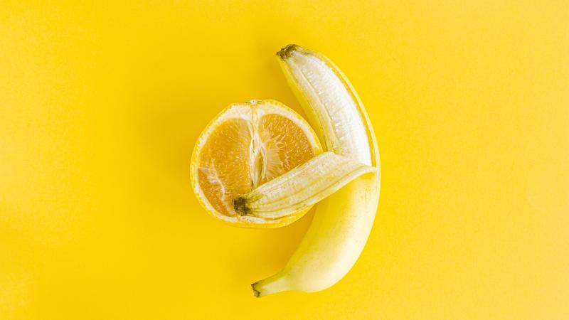 Puolikas appelsiini ja osin kuorittu banaani vierekkäin.