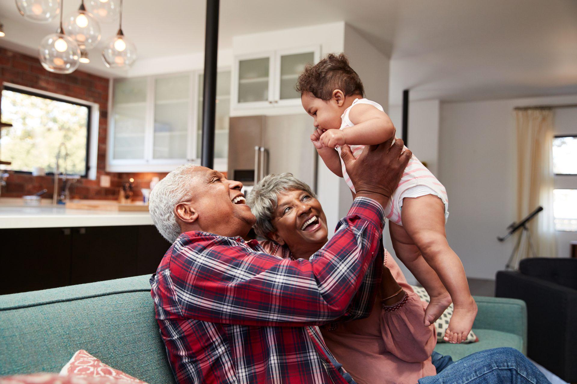 Isoisä nostaa lastenlastaan ilmaan ja isoäiti katsoo vierestä hymyillen.