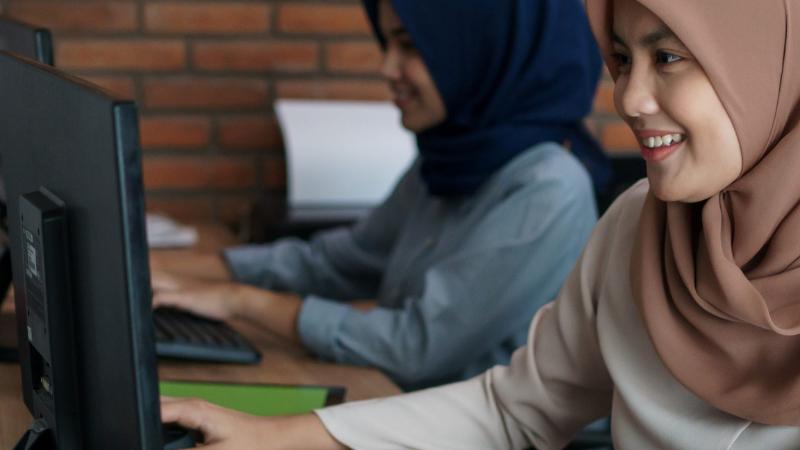 Kaksi nuorta naista tietokoneilla.