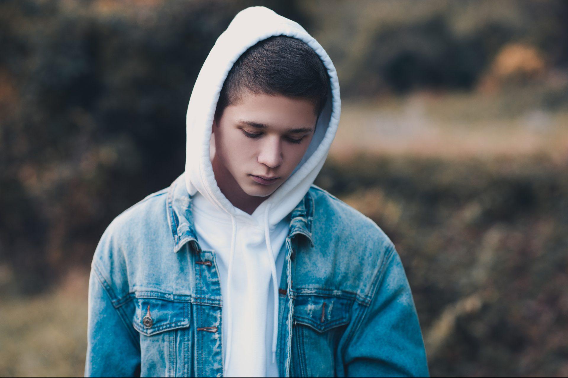 En pojke i ett höstlandskap står vänd mot kameran med blicken mot marken. Han har på sig en jeansrock och en munktröja, vars huva han dragit över huvudet.
