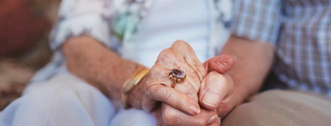 Kaksi ikääntynyttä ihmistä pitää toisiaan käsistä kiinni.