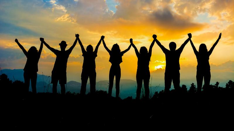 Joukko ihmisiä seisoo vasten auringonlaskua ja pitää toisiaan kädestä.