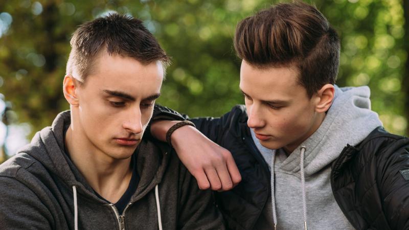 Kaksi nuorta poikaa keskustelevat vakavan näköisinä
