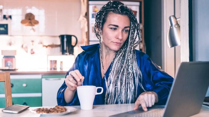 Pitktukkainen nainen katselee läppäriä pöydän ääressä, toisessa kädessä kahvikuppi. Istu keittiössä.