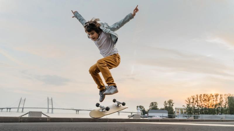 Poika hyppää skeittilaudan kanssa ilmaan tasaisella asfalttikentällä.