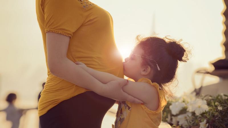 Lapsi pussaa äidin raskausmahaa.