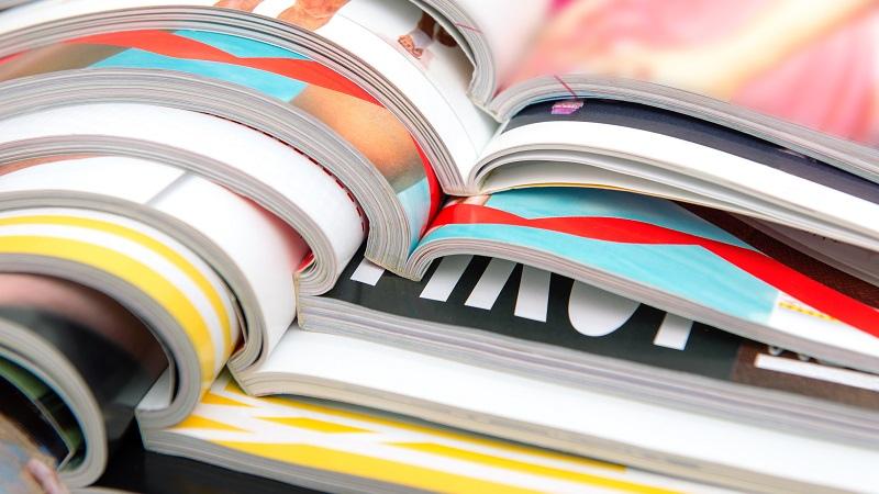 Värikkäitä aikakauslehtiä pinossa.