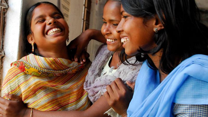 Kolme naista nauraa yhdessä
