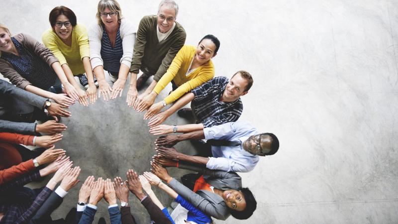 Joukko erilaisia uhmisiä seisoo yhdessä, ojennetut kämmenet muodostavat ympyrän.