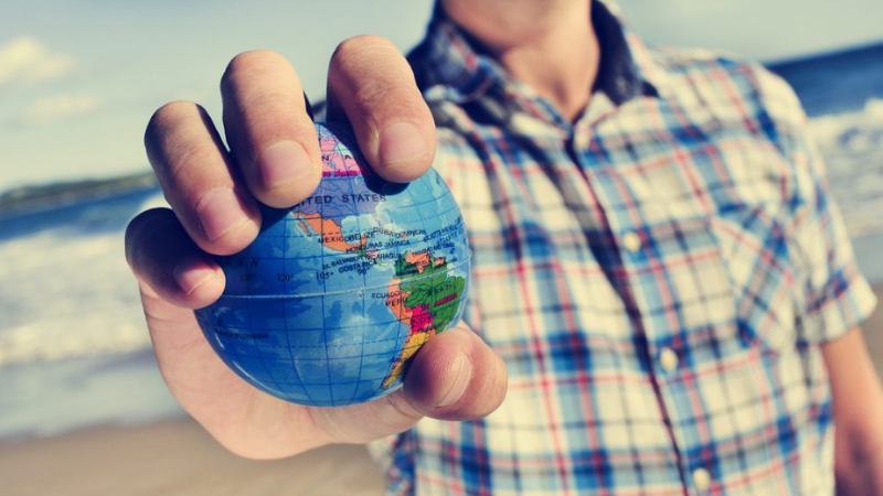 Mies seisoo rannalla, ruudullinen paita. Käsi ojennettu eteen ja kädessä pieni pallo, johon on kuvattu maapallo.