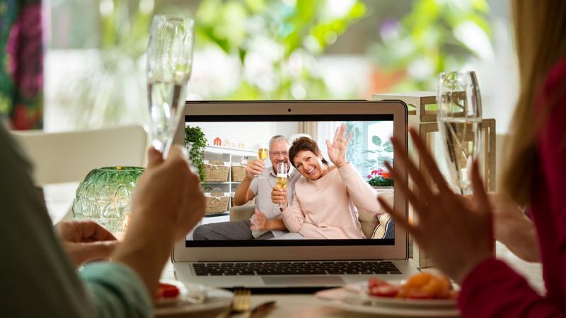 Kahden aikuisen videopuhelu vanhempien kanssa. Heillä on laseissa kuohuviiniä ja edessä ruokaa.