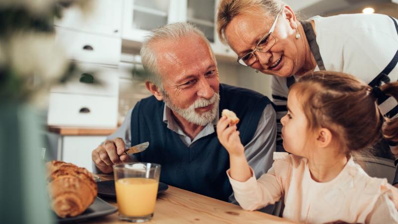 Ikääntynyt pariskunta ja pieni tytär aamupalapöydässä. Isovanhemmat kuuntelevat tyttöä iloisen näköisinä.