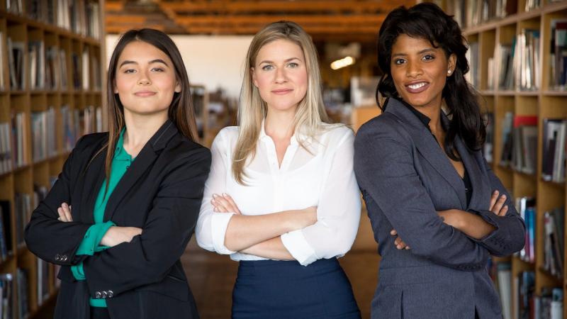 Kolme nuorta naista business-asuissa seisoo rivissä toimistossa, kaikilla kädet puuskassa ja itsevarma ilme.