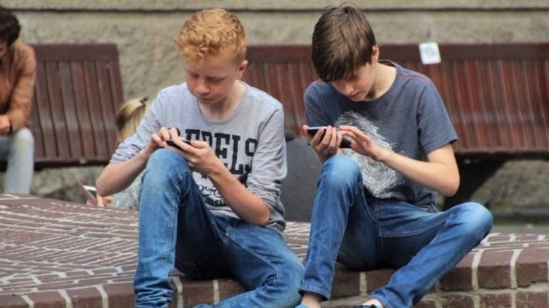 Kaksi poikaa katsoo kännyköitä istuen rappusilla.