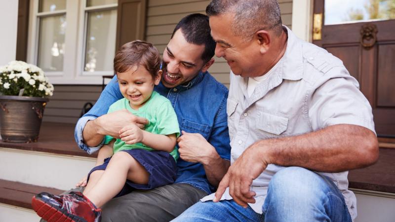 Talon kuistilla istuvat isoisä, hänen poikansa ja pojanpoikansa. Pieni poika istuu isänsä sylissä ja kaikki hymyilevät.